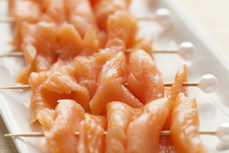 picks: Smoked salmon on cocktail picks with a pearl as a festive snack Stock Photo