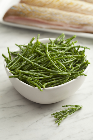 Fresh raw green samphire in a bowl with fresh fish in the background Stock Photo