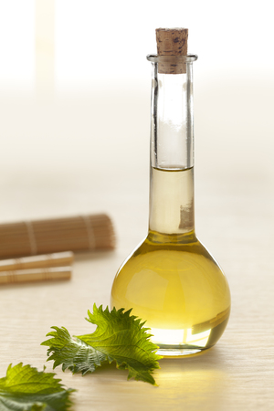 Bottle with shiso leaf oil and fresh leaves