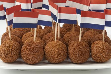 Schotel met Nederlandse traditionele snackbitterballen met een Nederlandse vlagcocktailstok