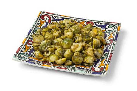 Moroccan dish with Brussels sprouts and preserved lemon on a modern dish on a white background Stock Photo