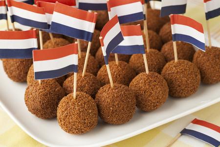 Collation traditionnelle néerlandaise bitterballen sur un plat avec un bâton de cocktail de drapeau néerlandais Banque d'images - 77054043
