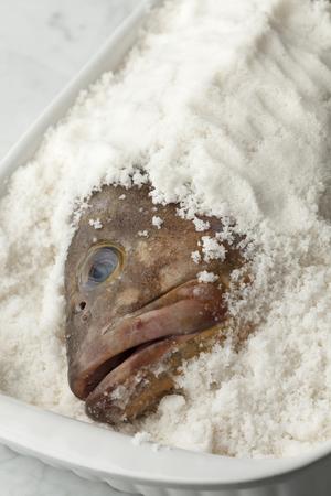 Dusky grouper fish in sea salt to make a salt crust Stock Photo