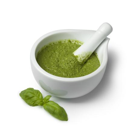Green homemade Italian pesto in a mortar on white background