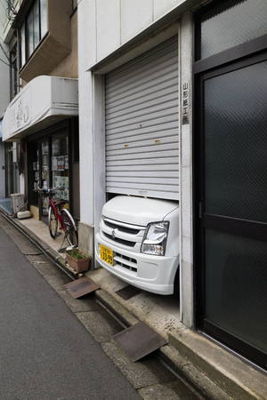 Kyoto, Japan -  May 23, 2017: Japanese car does not fit into the small garage in the street in Kyoto 新聞圖片