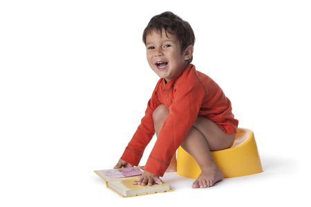 Toddler boy sitting on a potty and with a book on white background