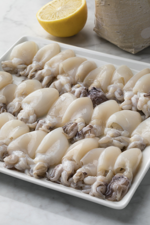 Fresh cleaned raw baby squid on a dish Stock fotó - 97034976