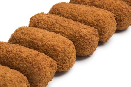 Rij van gefrituurde Nederlandse kroketten die op witte achtergrond wordt geïsoleerd Stockfoto