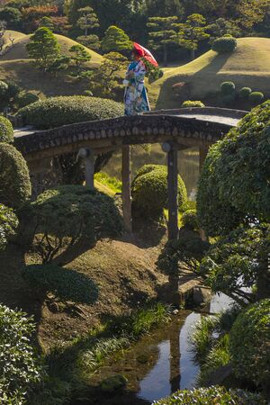 Kumamoto, Japan - November 11, 2018: Arched bridge and traditional dressed Japanese woman in Suizenji Garden, Suizenji Jōjuen Editorial