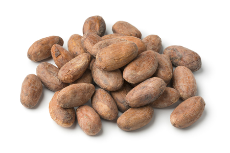 Heap of whole cocoa beans close up isolated on white background