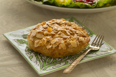 Single fresh baked traditional Moroccan small bastella with roasted almond topping