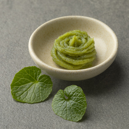 Dish with traditional Japanese horseradish paste and fresh wasabi leaves