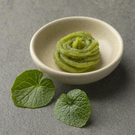 Plato con pasta de rábano picante tradicional japonesa y hojas frescas de wasabi