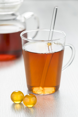 Glass of hot tea with yellow honey pearls