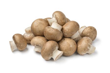 Heap of fresh raw chestnut mushrooms close up isolated on white background