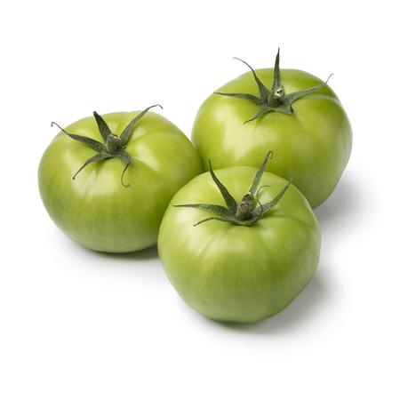 Three fresh green unripe tomatoes isolated on white background