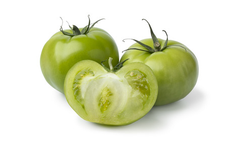 Whole and halved fresh green unripe tomatoes isolated on white background