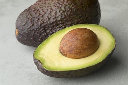 Fresh whole and half ripe avocado fruit closeup Фото со стока