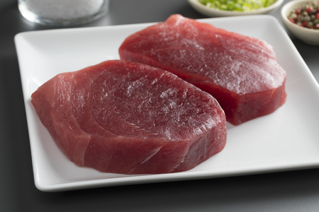 Dish with two fresh raw yellowfin tuna steaks close up