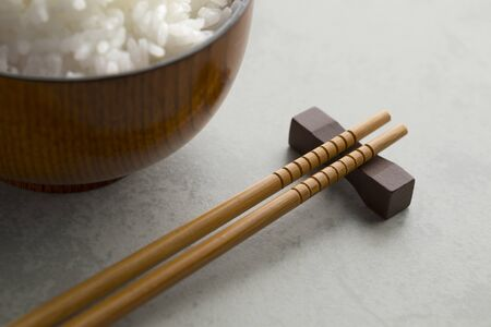 Traditional Japanese wooden chopsticks and a bowl with white rice in the background Stock Photo