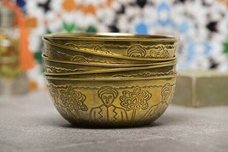 Stack of gold colored metal Hammam water bowls