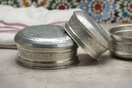 Drying stack of silver colored metal water bowls in Hammam