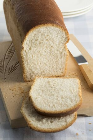 Fresh baked loaf of white bread cut into slices on a cutting board
