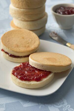 Dutch beschuitbollen, crispy baked roll, with red strawberry jam for breakfast