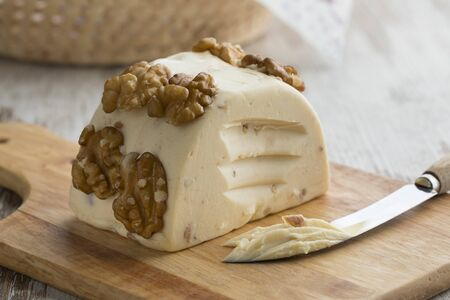 Piece of soft walnut cheese on a cutting board close up Stockfoto