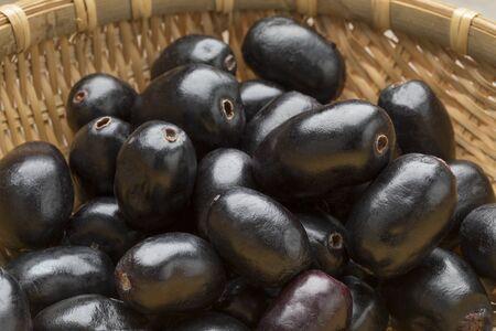 Whole fresh Jamun berries in a basket Фото со стока