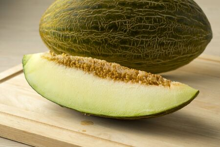 Piece of Piel de sapo melon and seed close up with a whole one at the background Фото со стока