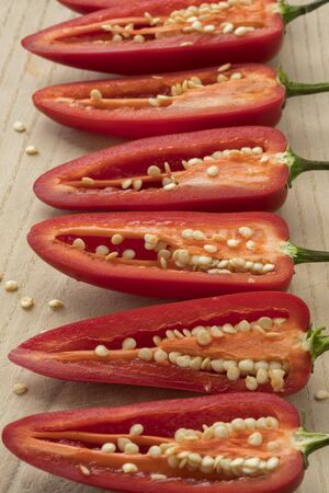 Row of halved red Jalapeno pepper with seeds