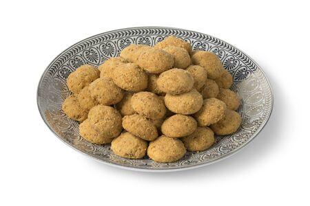 Dish with traditional homemade Moroccan festive ghoriba cookies isolated on white background