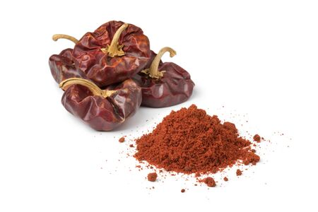 Nora, spanish dried peppers and a heap of ground powder isolated on white background