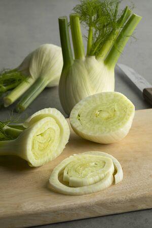 Fresh raw organic fennel bulb and slices on a cutting board