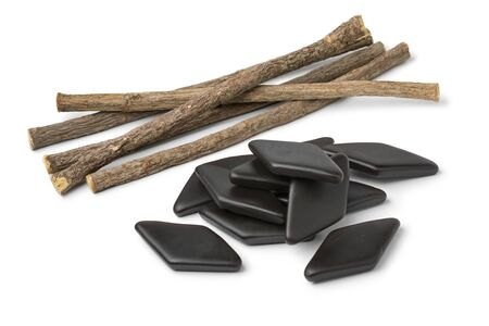 Heap of dried Licorice roots and black salt licorice confectionary, a Dutch treat, isolated on white background Фото со стока