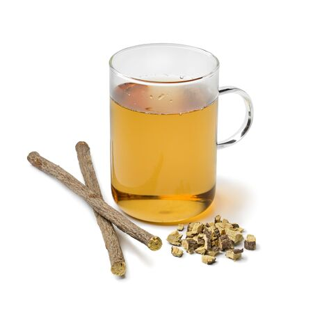 Glass of licorice tea and pieces of roots isolated on white background