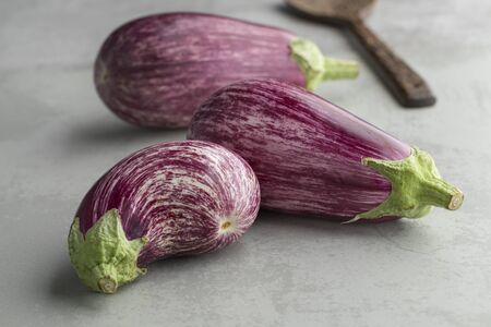 Heap of fresh raw purple striped eggplants close up