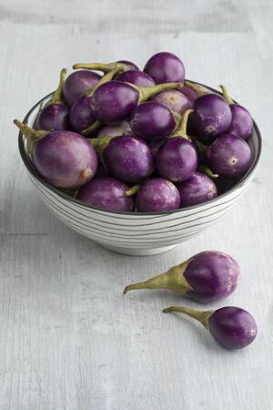 Bowl with fresh raw purple mini eggplants as a snack