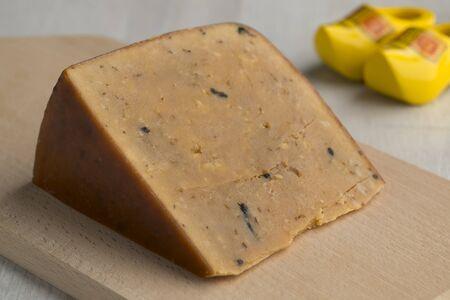 Piece of Dutch very mature Frisian Clove Cheese on a cutting board