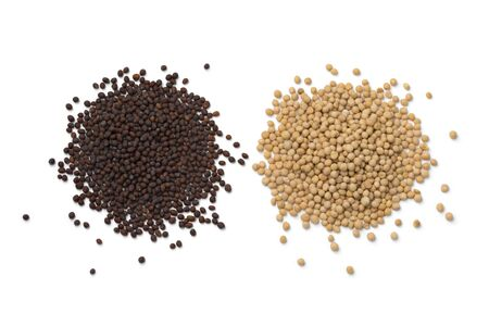 Heap of yellow and brown mustard seed isolated on white background