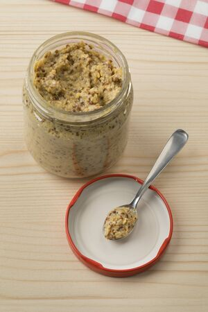 Glass jar with traditional Dutch coarsely ground mustard close up