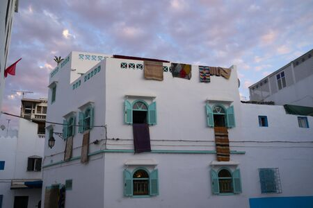 Traditional Moroccan carpets hanging on the facade of a carpet store in twilight in Asilah, North Morocco