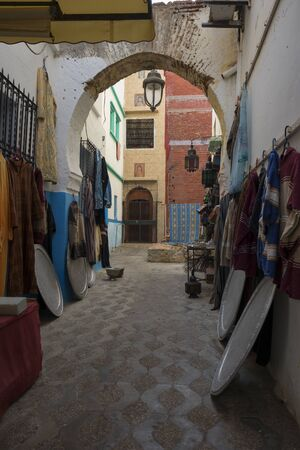 Narrow old street  with merchandise in the medina of Asilah, Morocco