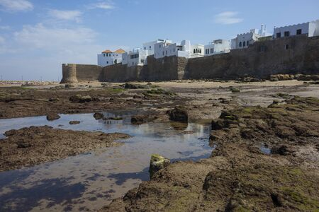 Low tide in the Atlantic Ocen in front of the historical rampart to protect Assilah, Morocco Фото со стока