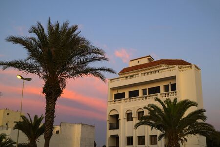 Traditional built apartments with palm trees at the boulevard of Assilah at twilight 版權商用圖片