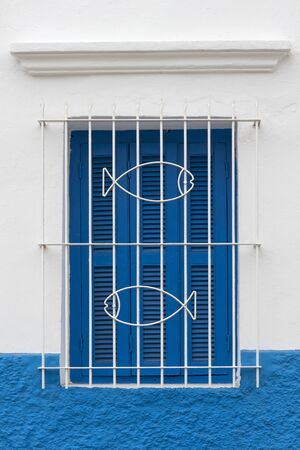 Traditional Moroccan window protected with blue shutters and metal railing decorated with fishes in Asilah, Morocco