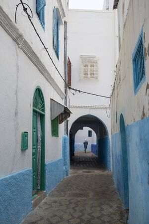 Narrow old street and gate in the medina of Asilah, Morocco