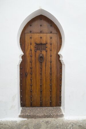 Old wooden door with brass decoration in the medina of Asilah, Morocco Reklamní fotografie