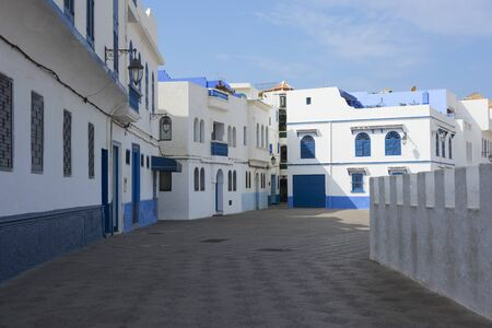 Old street  in the medina of Asilah with at one side the stone rampart to the beach